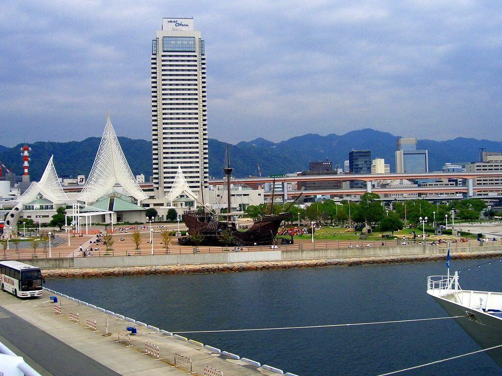 35階建ての白くて高いホテルオークラと手前に三角の網目が特徴的な神戸海洋博物館屋外展示の黒い木造船が見えるオリエンタルホテルロビー前からの画像