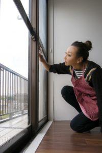 窓を掃除する女性